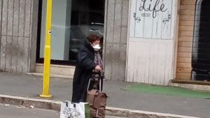 Sicurezza, Donna con mascherina aspetta l'autobus a Roma